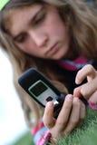 Chica joven y teléfono celular imagen de archivo libre de regalías