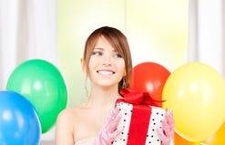 Chica marchosa con los globos y la caja de regalo Foto de archivo libre de regalías