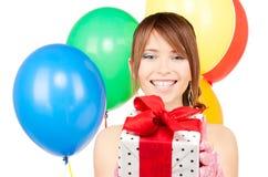 Chica marchosa con los globos y la caja de regalo Fotos de archivo