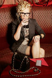 Chica marchosa que bebe martini en el sofá rojo Fotografía de archivo
