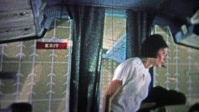 CHICAGO - 1966: Asistente de vuelo ocupado que sirve a los clientes con una sonrisa linda almacen de video