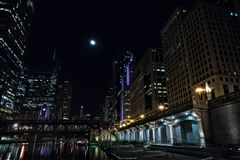 Chicago city riverwalk promenade at night with vintage bridge. Chicago city riverwalk promenade at night with vintage drawbridge, illuminated urban downtown Royalty Free Stock Images