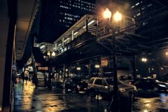 Chicago city street scene in the Loop at night. Chicago city street scene in the Loop with elevated CTA L train platform, stairs, pedestrians and cars at night Stock Images