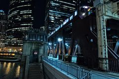 Chicago city vintage river drawbridge with train at night. Chicago city vintage river drawbridge with elevated CTA subway train and urban downtown buildings at Royalty Free Stock Image
