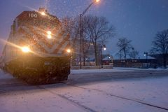 Chicago commuter train arriving in winter snowstorm. Evening blustery winter scene of Chicago suburban commuter train arriving at platform in snowstorm Stock Image