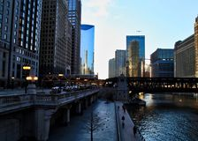 Chicago downtown during evening commute as an El train passes over Chicago River. Chicago downtown during evening commute on a late February winter evening. El Stock Photos