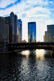 Chicago downtown during sunset and evening commute as an El train passes over Chicago River. Chicago downtown during sunset and evening commute on a late Royalty Free Stock Image