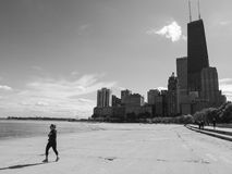 Chicago Gold Coast Beach. CHICAGO, IL, USA - OCTOBER 5, 2014: Woman runs along the beach of the Chicago Gold Coast with downtown skyscrapers in the background in Royalty Free Stock Images