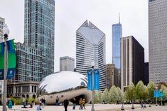 Chicago, IL - 5 de mayo de 2011 - núblese la puerta Bean Sculpture en parque del milenio con los turistas y la vista de la arquit foto de archivo