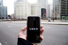 Chicago, IL die, de V.S., februari-21.2017, Mens een smartphone met open Uber app in de stad voor redactie slechts gebruik houden stock afbeeldingen