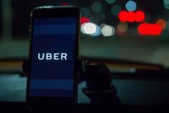Chicago, IL, los E.E.U.U., Feb-21,2017, Smartphone ató a un soporte del coche en coche con el logotipo de Uber en la noche para e Imagen de archivo