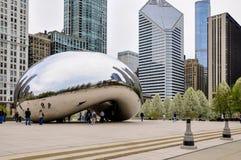 Chicago, IL - 5. Mai 2011 - bewölken Sie Tor Bean Sculpture im Jahrtausend-Park mit Touristen und Ansicht von Chicago-` s Archite Lizenzfreie Stockfotografie