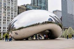 Chicago, IL - 5. Mai 2011 - bewölken Sie Tor Bean Sculpture im Jahrtausend-Park mit Touristen und Ansicht von Chicago-` s Archite Lizenzfreie Stockbilder