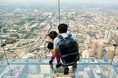 Skydeck Chicago Willis Tower. CHICAGO, IL - SEPTEMBER 2, 2017 : Father and daughter on the ledge at the Skydeck of the Willis Tower. The Skydeck is on 103rd Royalty Free Stock Photos