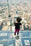 Skydeck Chicago Willis Tower. CHICAGO, IL - SEPTEMBER 2, 2017 : Little girl is standing on the ledge at the Skydeck of the Willis Tower. The Skydeck is on 103rd Royalty Free Stock Photo