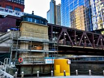 Elevated `el` train passes over Chicago River. Bridgehouse is under repair. City of Chicago sign upside-down. Royalty Free Stock Image