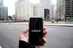 Chicago IL, USA, Feb-21,2017, man som rymmer en smartphone med öppna Uber app i staden för redaktörs- bruk endast Arkivbilder