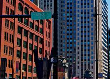 Statue of man on tightrope on Kinzie Street in Chicago, with pedestrian walk sign. stock photos