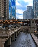 View of elevated `el` train crossing over Wacker Drive, Chicago River, and Wells Streets at rush hour while commuters hurry along. Chicago, IL / USA - 4/3/18 Royalty Free Stock Photos