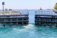 Chicago lock. Chicago, USA - May 24, 2014: Chicago lock gates are opening to Lake Michigan. Water running into the lock Royalty Free Stock Images