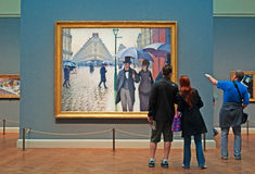 Chicago: looking at oil painting Paris Street Rainy Day by Gustave Caillebotte at Art Institute of Chicago on September 23, 2014 Stock Images