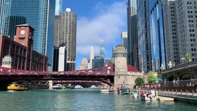 Chicago morning on river and riverwalk, where people take advantage of the city`s waterway on water taxis, tourboats