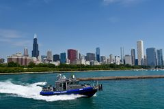 Chicago Police Boat. This is a Summer picture of a Chicago Police Boat in action on Lake Michigan with the iconic Chicago skyline in the background off The Shedd Stock Photos