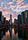 Chicago River stunningly reflects cityscape after a winter storm as clouds clear and sun begins to set. Tump Tower in center stock image