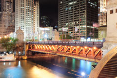 Chicago River Walk. With urban skyscrapers and bridge illuminated with lights and water reflection at night Royalty Free Stock Photo
