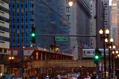 Commuters travel on LaSalle Street while Chicago`s Elevated `el` Train passes through the Loop at Sunset Royalty Free Stock Images