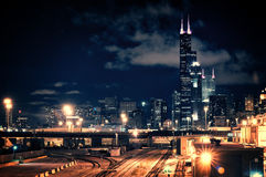 Chicago skyline cityscape at night featuring a train yard and ur. Ban bridge with a dramatic cloudy sky stock photography