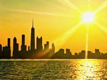 Chicago skyline seen from Lake Michigan, with sunset and sunbeams extending over cityscape during summer. View of Chicago skyline seen from Lake Michigan, with royalty free stock photography