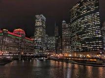 Chicago-Stadtbild belichtet mit den Weihnachtsfeiertagsdekorationen und Stadtnachtlichtern, die über den Fluss nachdenken Stockfotografie