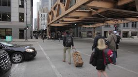 Chicago street scene with tracks overhead. Foot traffic in Chicago, 1080p, infrastructure stock video footage