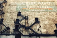Chicago Theater. Сhicago, USA - June 17, 2017: Old faded advertising and fire escape on the side of the Famous Chicago Theater on East Benton Place late in the Stock Photos