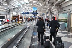 CHICAGO, USA - APRIL 1, 2014: Pilots walk to gate at Chicago O 'Hare International Airport in USA. It was the 5th busiest airport. In the world with 66,883,271 stock image