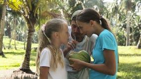Chicas jóvenes con el jugo de consumición del coco del padre almacen de video