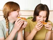 Chicas jóvenes con la consumición de la pizza Foto de archivo libre de regalías