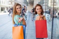 Chicas jóvenes con los panieres coloridos Estación de ventas Imagenes de archivo