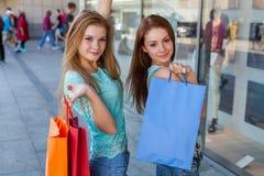 Chicas jóvenes con los panieres coloridos Estación de ventas Imagen de archivo libre de regalías