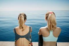 Chicas jóvenes de la aptitud que se relajan después de correr en ciudad fotografía de archivo
