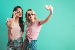 Chicas jóvenes diversas felices que toman el selfie con smartphone contra la pared azul imagenes de archivo