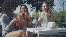 Chicas jóvenes elegantes que tienen bebidas afuera metrajes