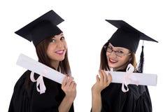 Chicas jóvenes en capa del estudiante con el diploma Imagenes de archivo