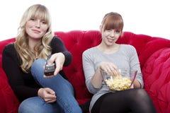 Chicas jóvenes en el sofá rojo con el telecontrol y palomitas Fotos de archivo libres de regalías
