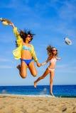 Chicas jóvenes en el traje de baño que salta en la playa Fotos de archivo libres de regalías