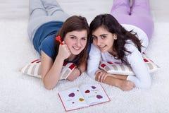Chicas jóvenes en la escritura del amor en un diario Fotos de archivo