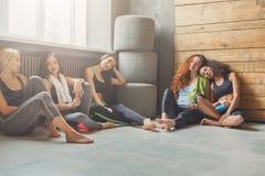 Chicas jóvenes en la ropa de deportes que tiene resto después del entrenamiento de la aptitud Imágenes de archivo libres de regalías