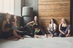Chicas jóvenes en la ropa de deportes que tiene resto después del entrenamiento de la aptitud Imagen de archivo