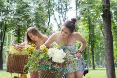 Chicas jóvenes en las bicicletas con las flores Imagen de archivo libre de regalías
